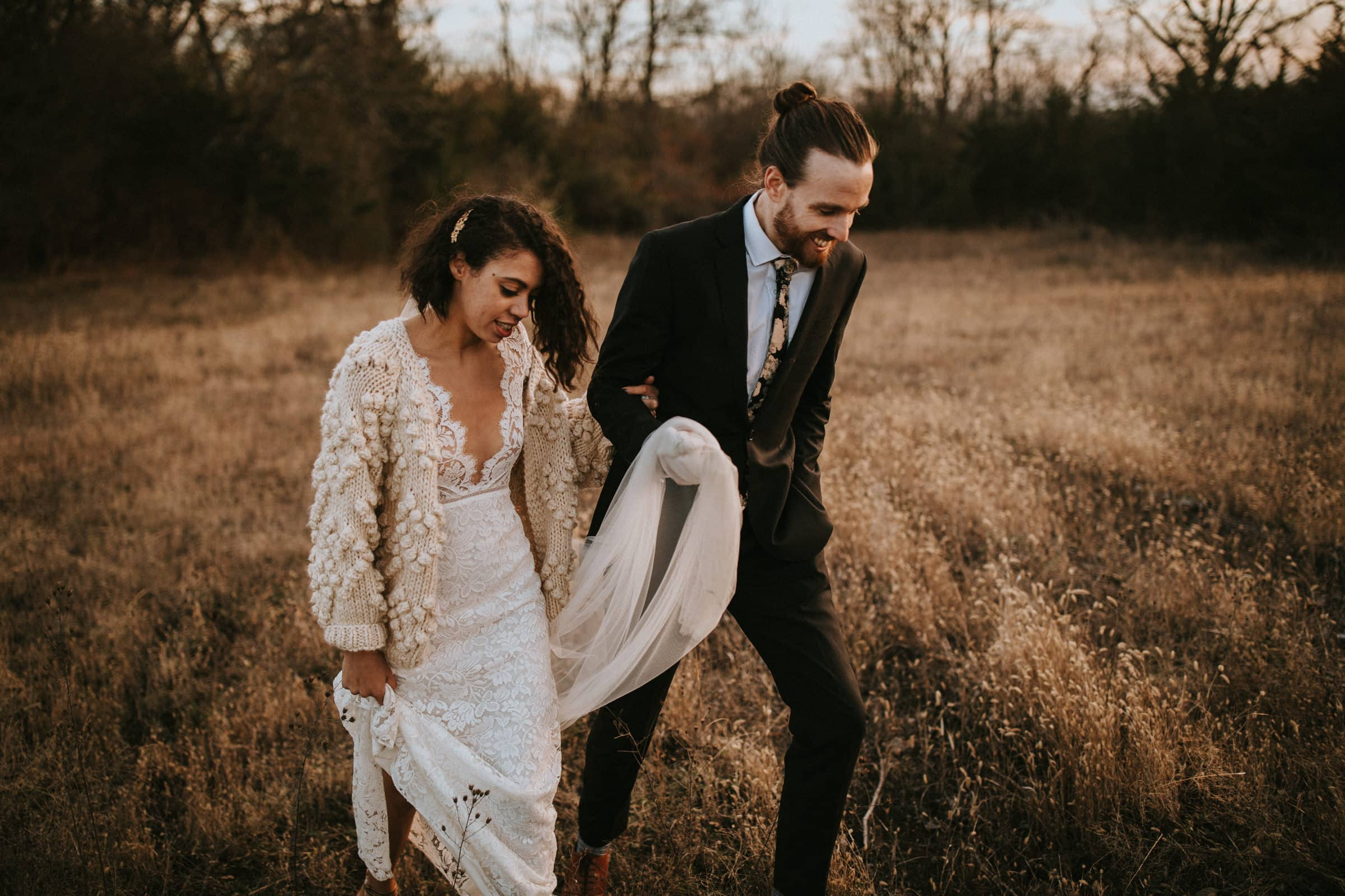 The wedding couple is walking through a dry meadow.