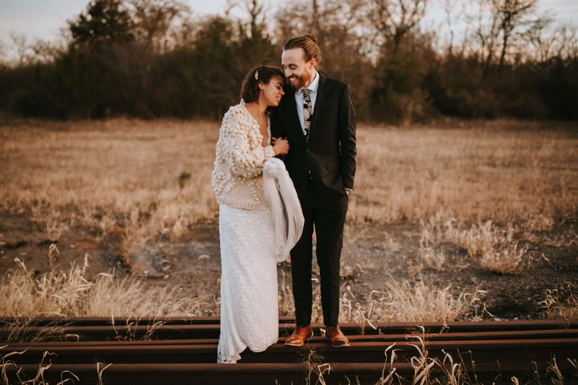The wedding couple is standing on old tram tracks.