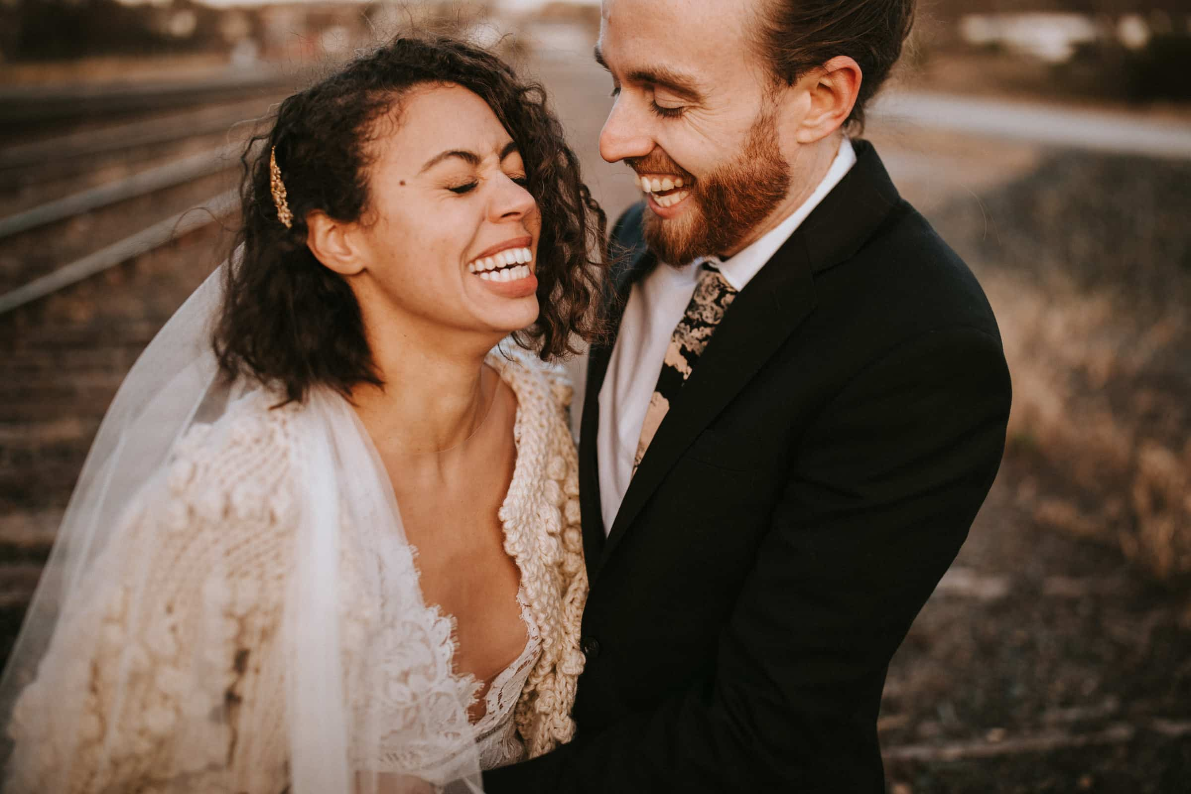 The closeup shows a wedding couple holding each other and laughing at each other.
