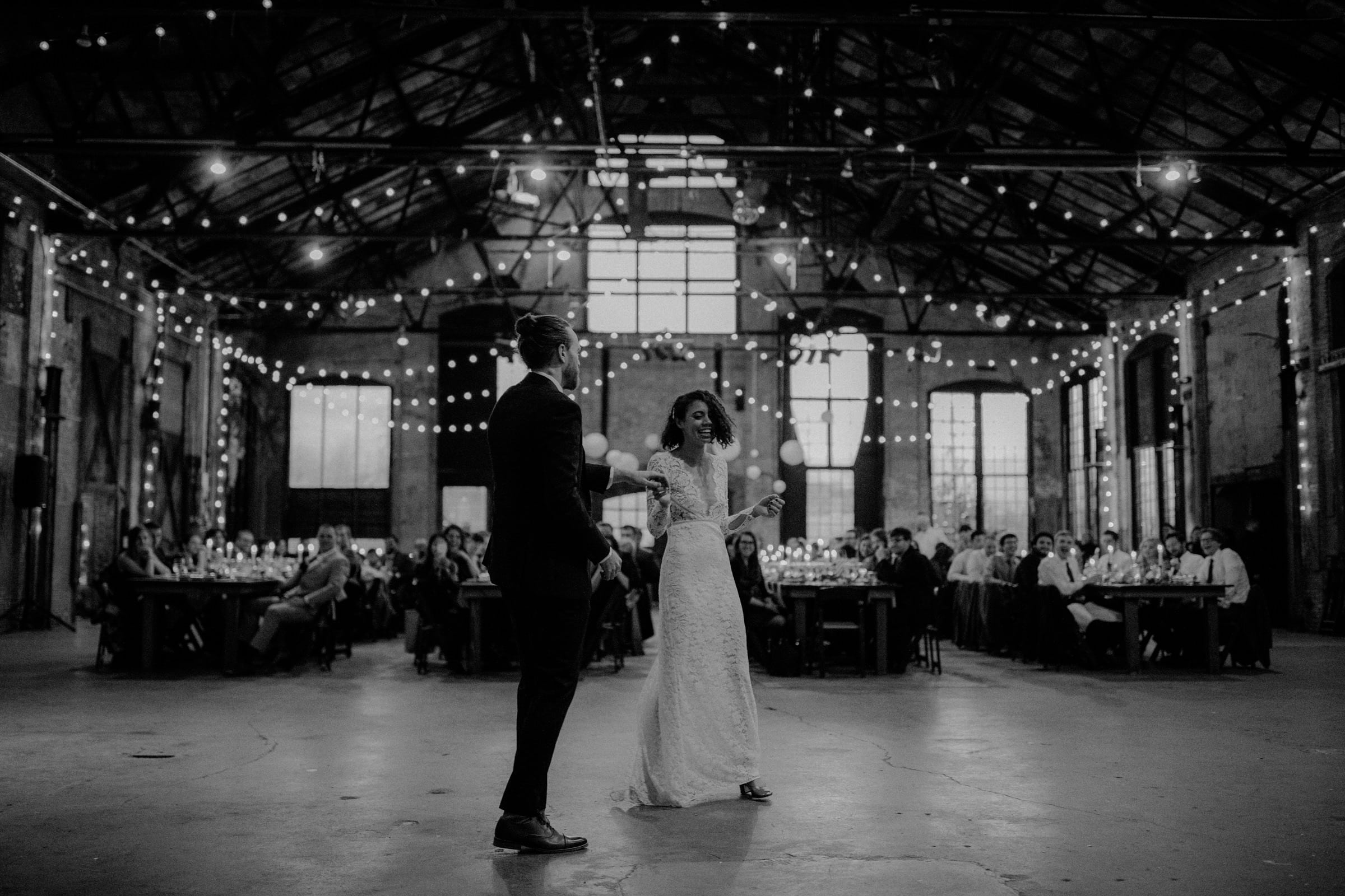 The wedding couple is about to dance in a big industrial hall.