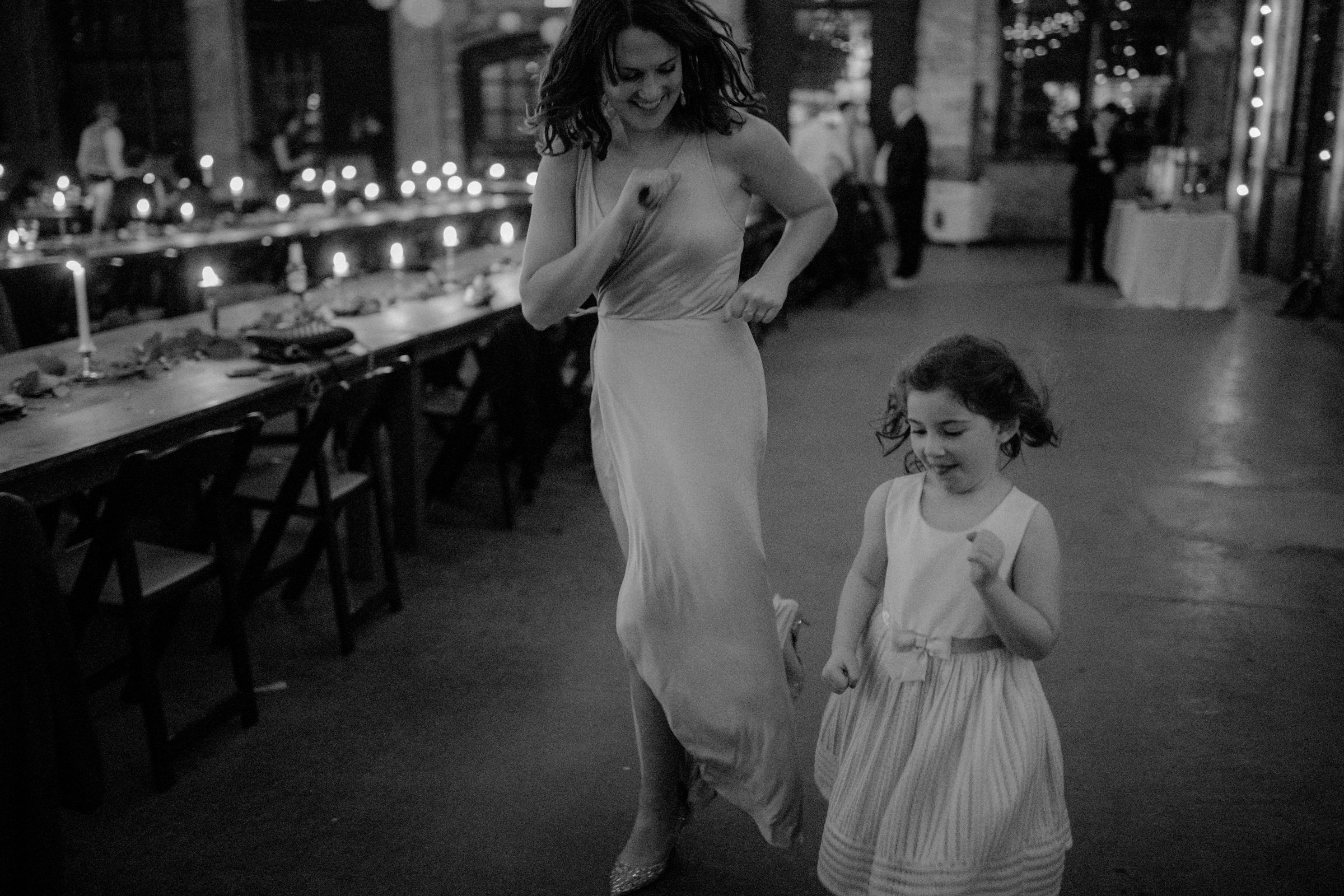 A wedding guest and a little girl are running along the wedding tables.