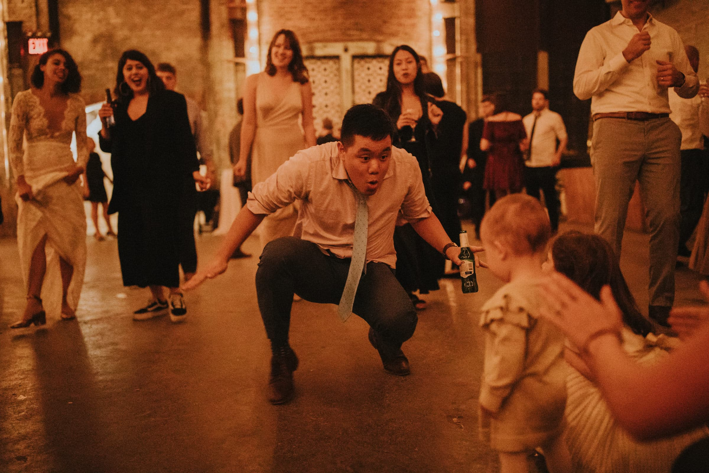 A wedding guest is dancing with children.