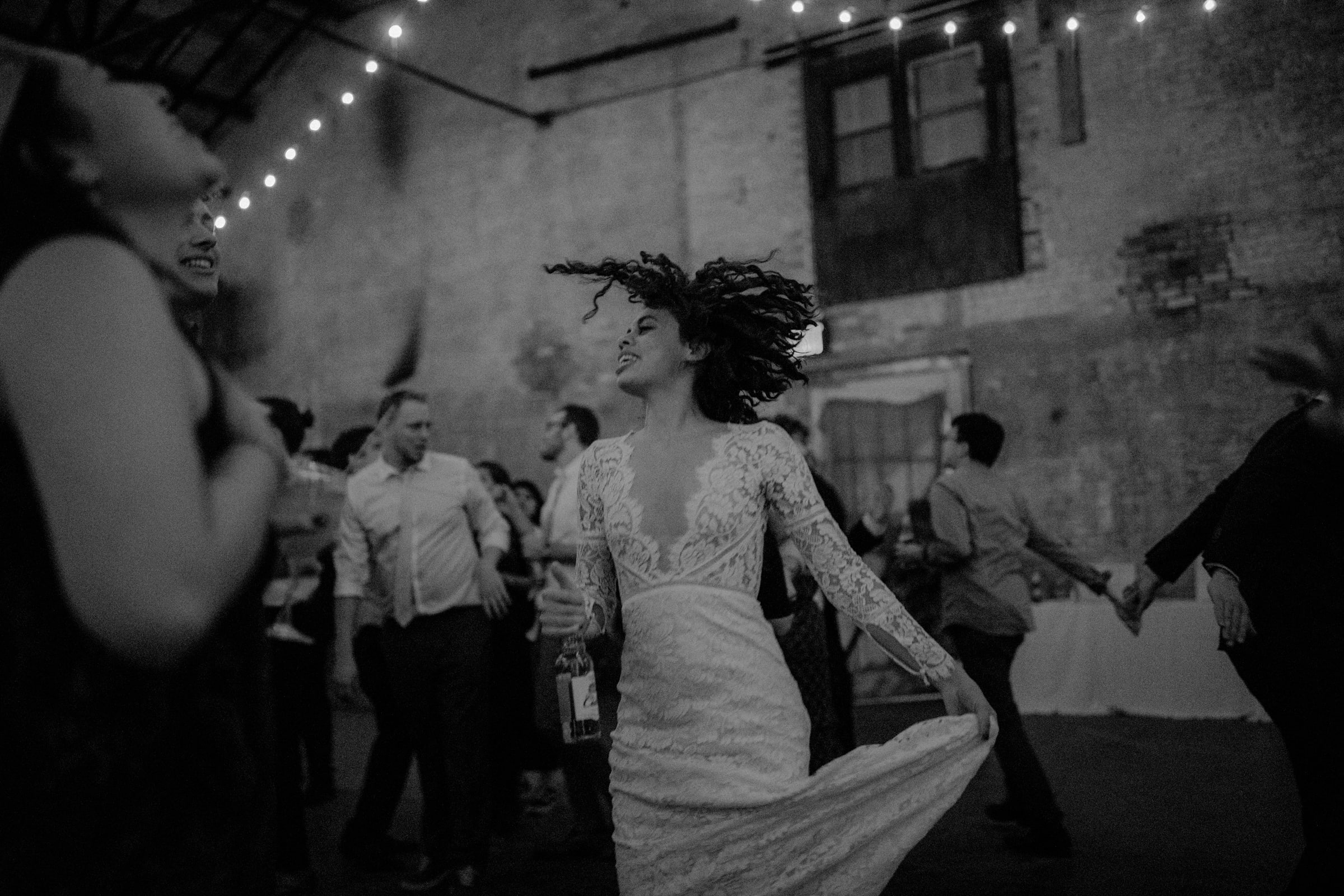 The bride is dancing with other wedding guests.