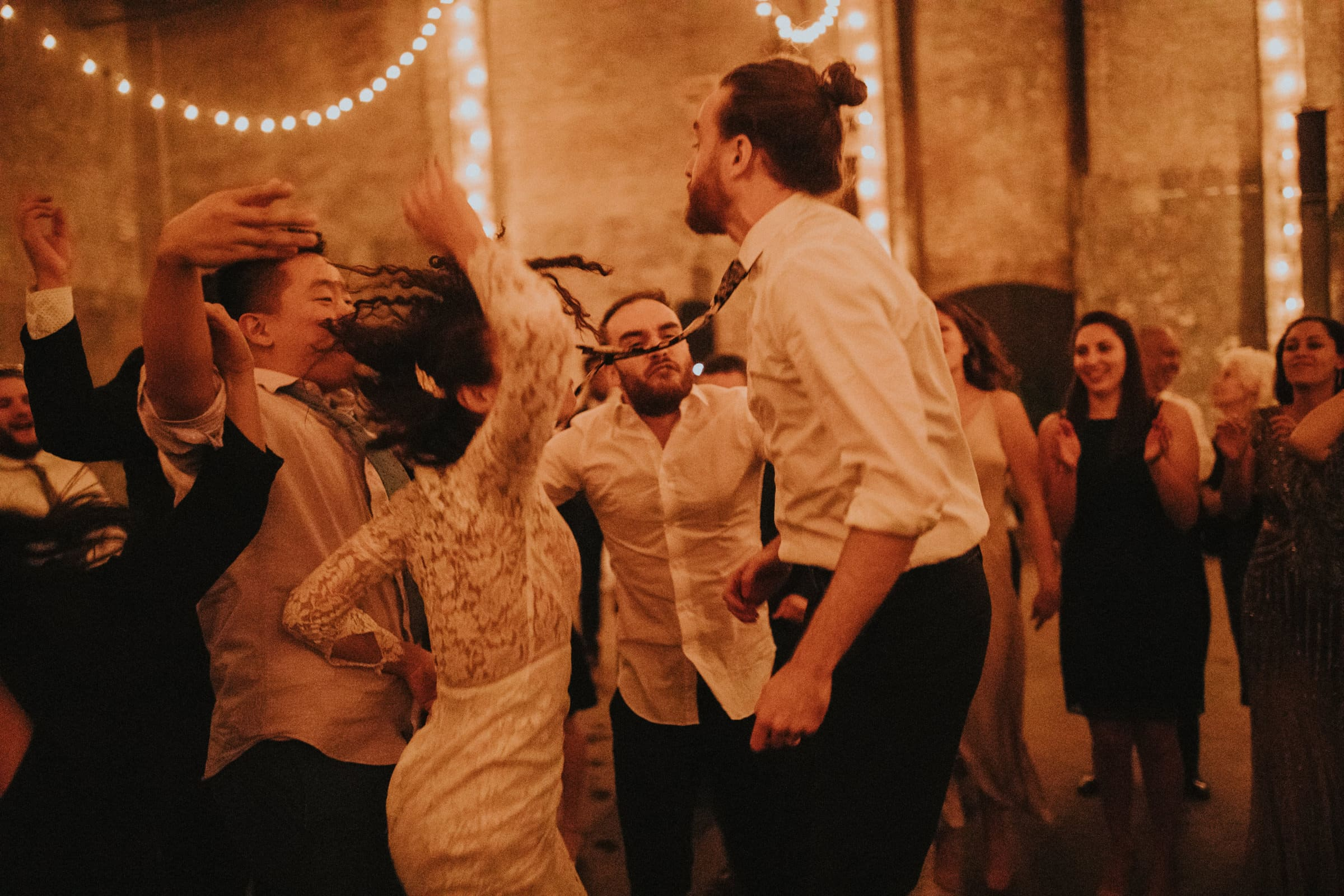 The wedding couple is dancing with their guests at the wedding.