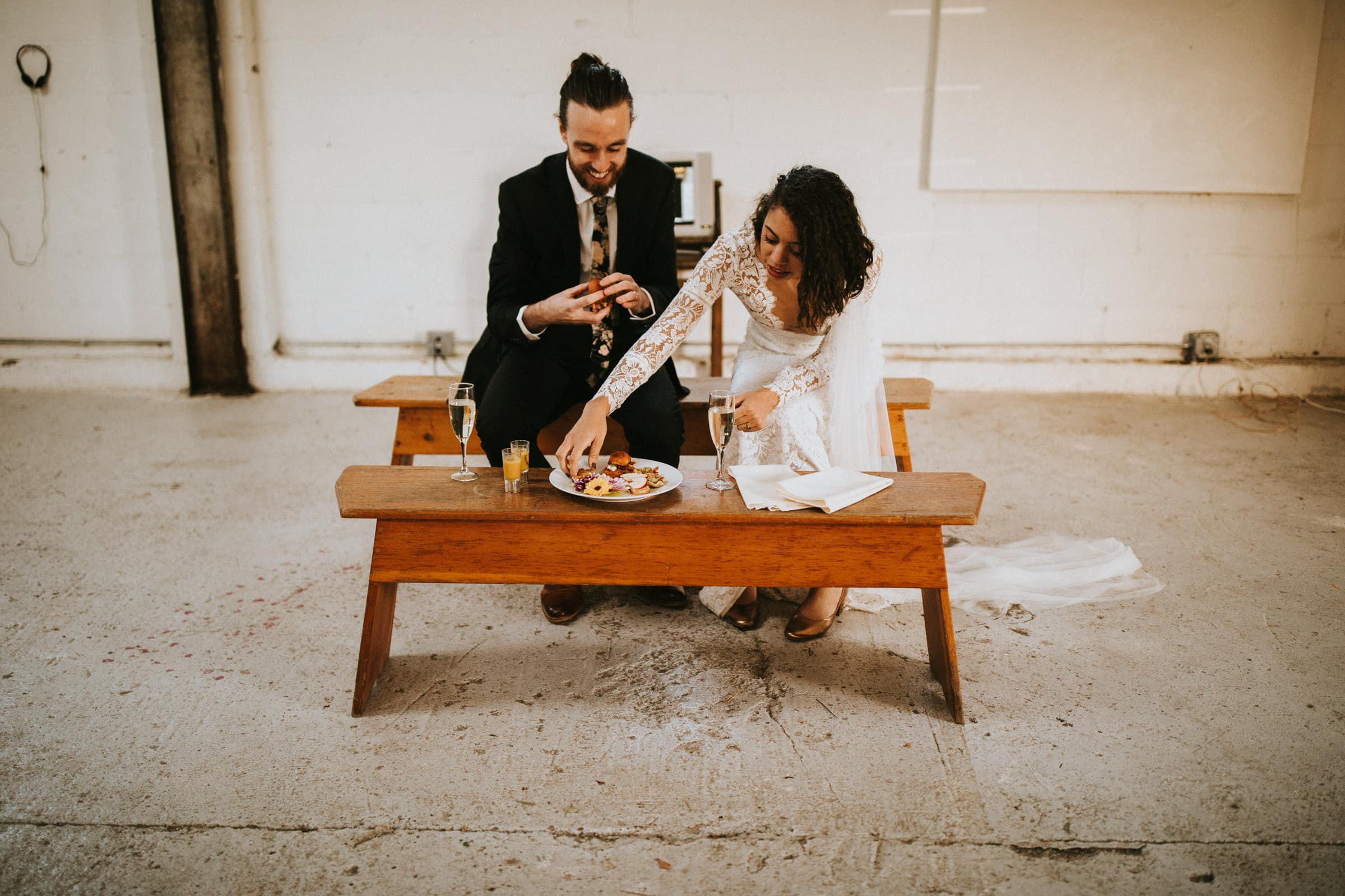 The wedding couple is sitting on a small bench and is eating snacks and drinking champaign.
