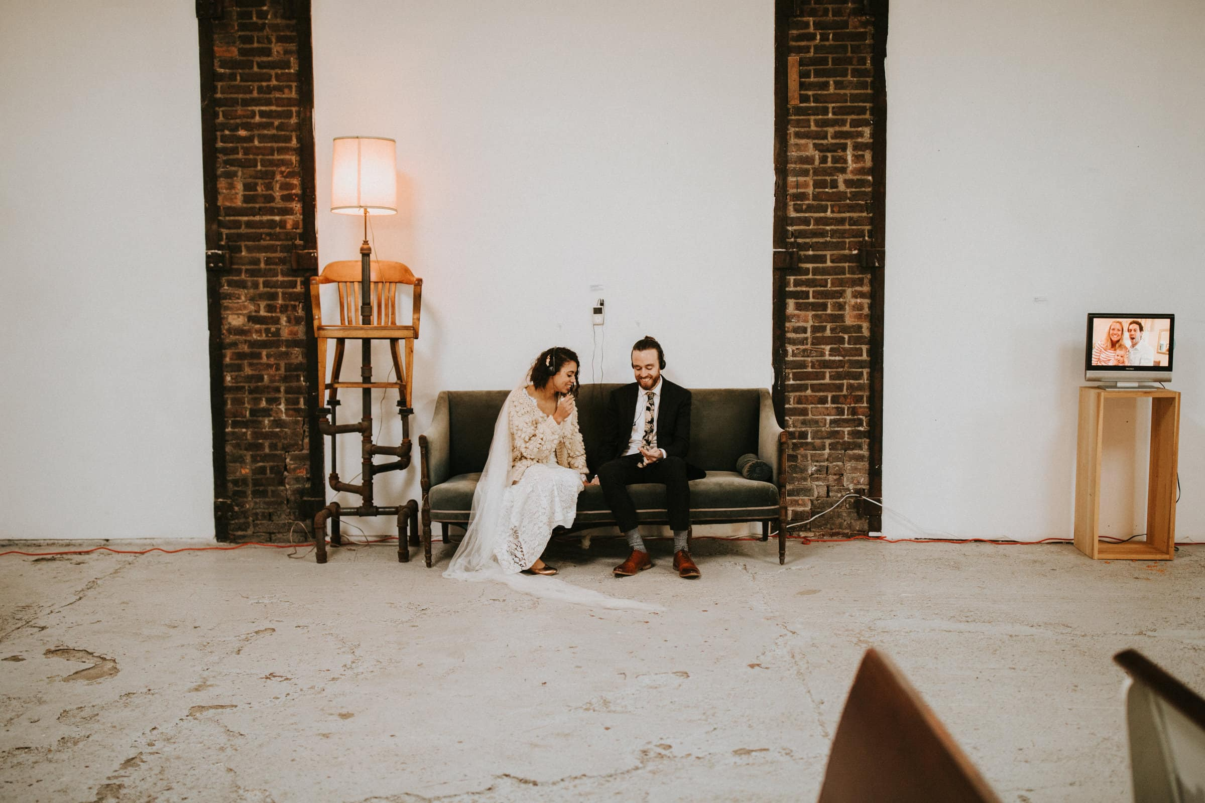 The wedding couple is on a sofa and listening to a podcast from their friends.