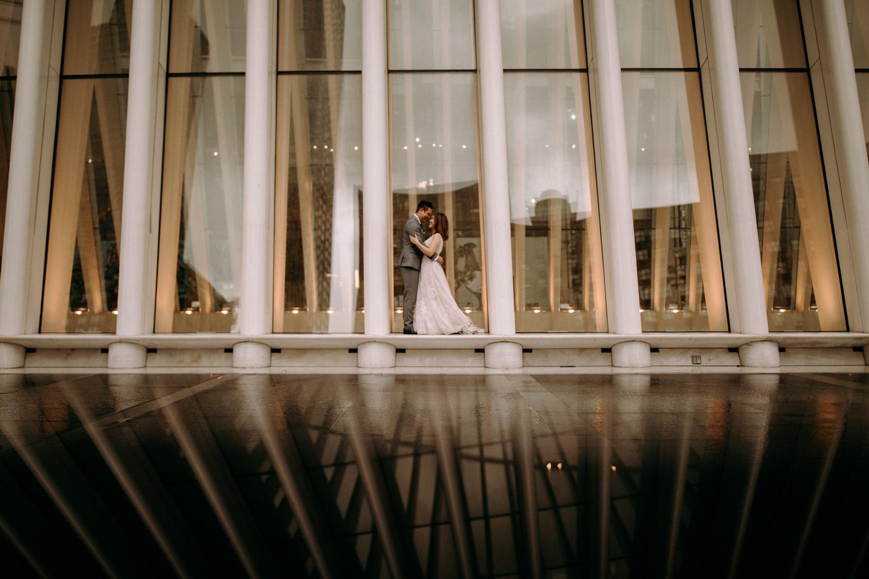 The wedding couple is standing between columns of a huge building.