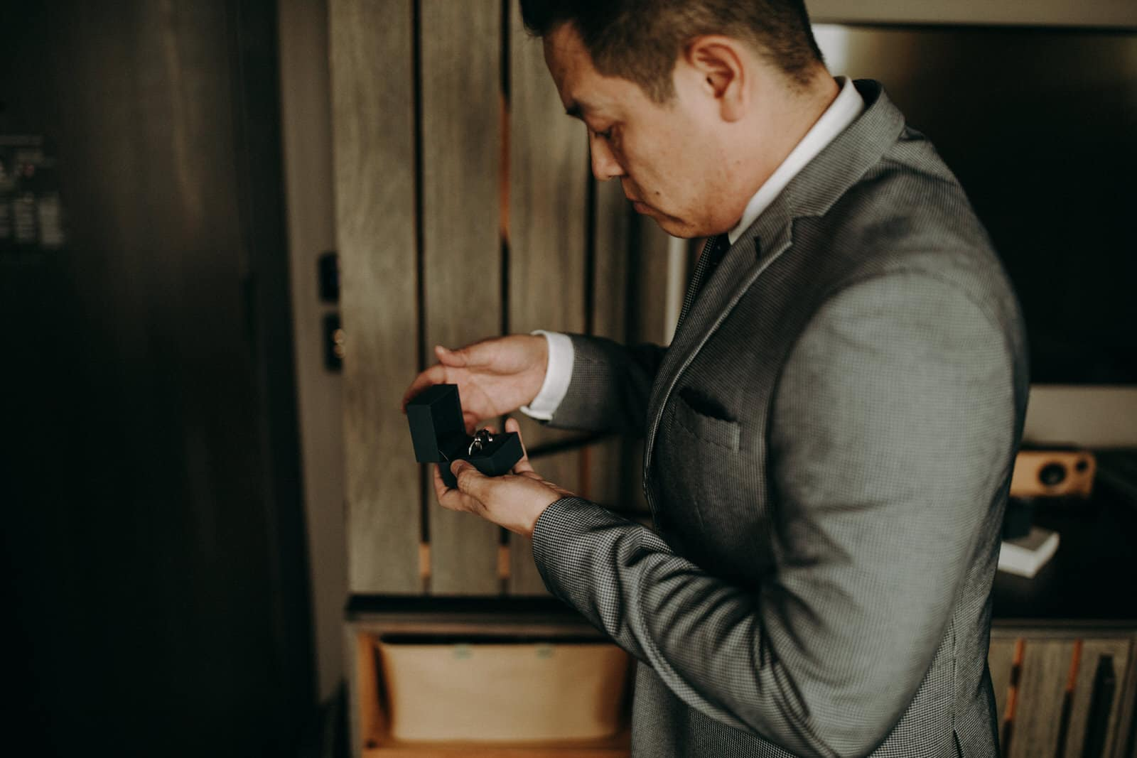 The groom is looking at the two wedding rings.