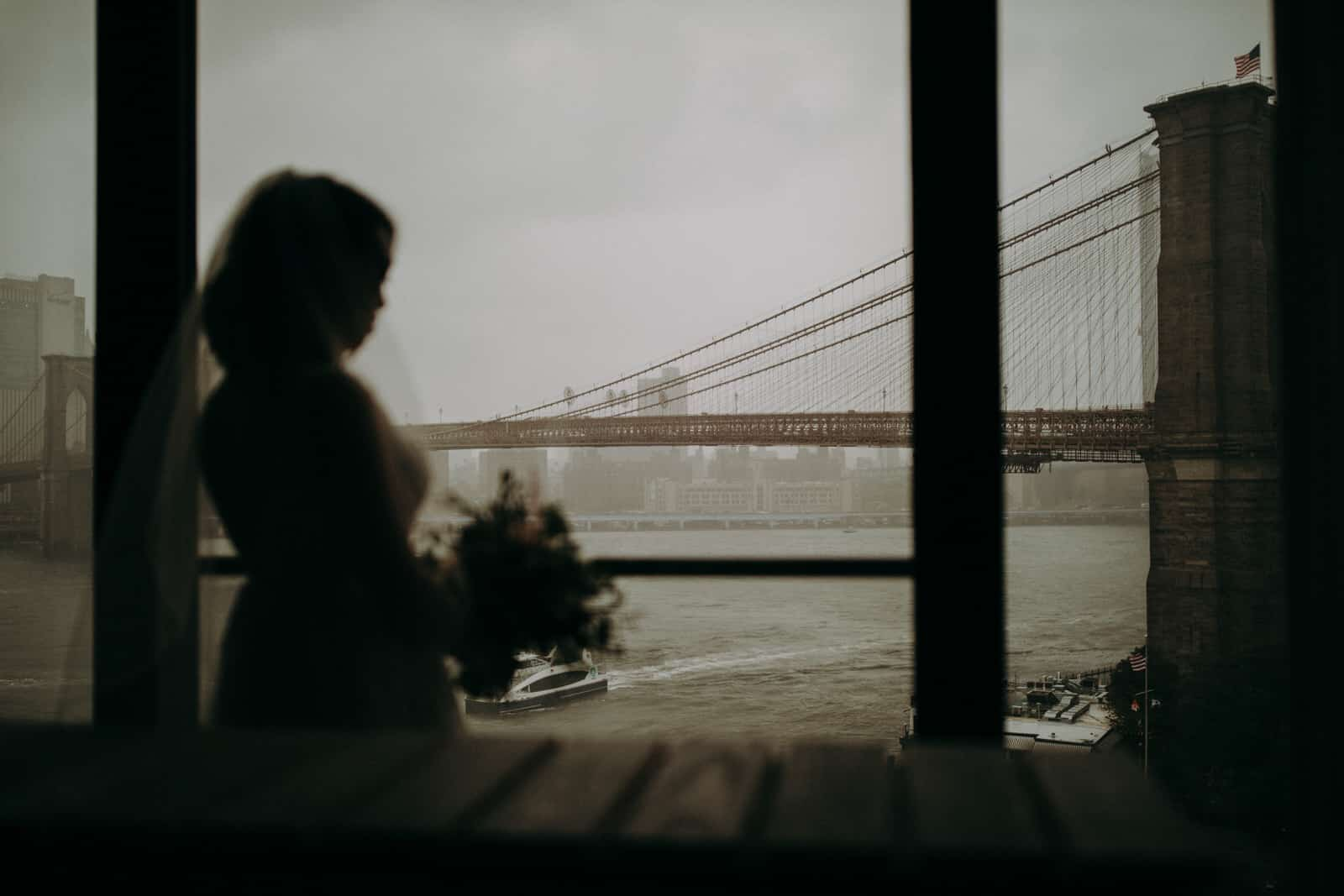 The bride is holding a flower bouquet and is looking out of the window at the Brooklyn Bridge.