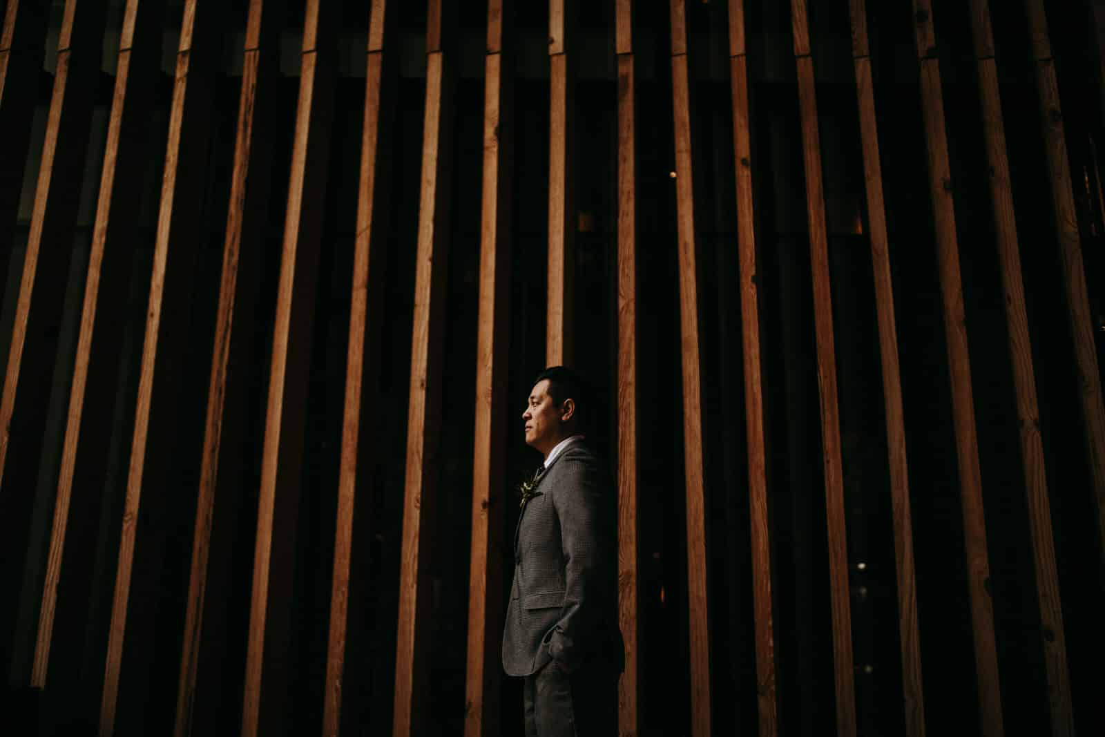 The groom is standing in front of a building with vertical wooden battens.