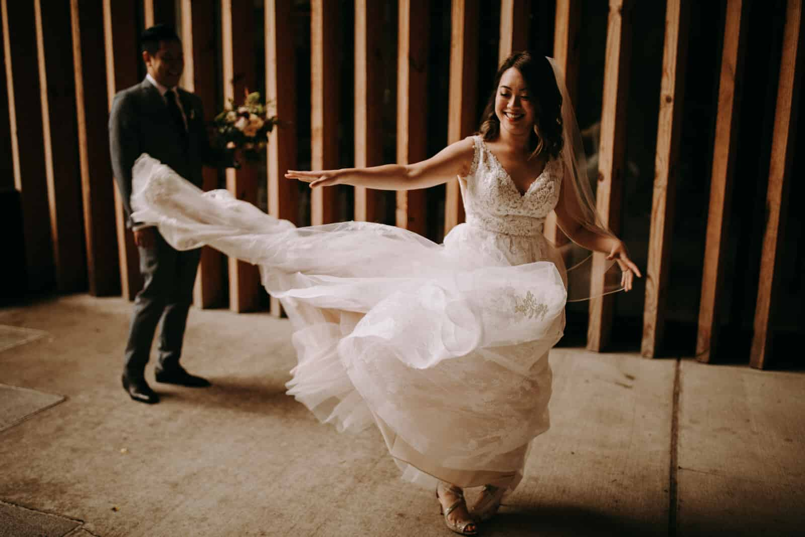 The bride is throwing her dress in the air and the groom is standing behind her.
