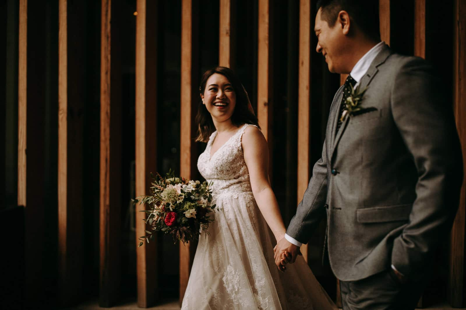 A wedding couple is holding hands.