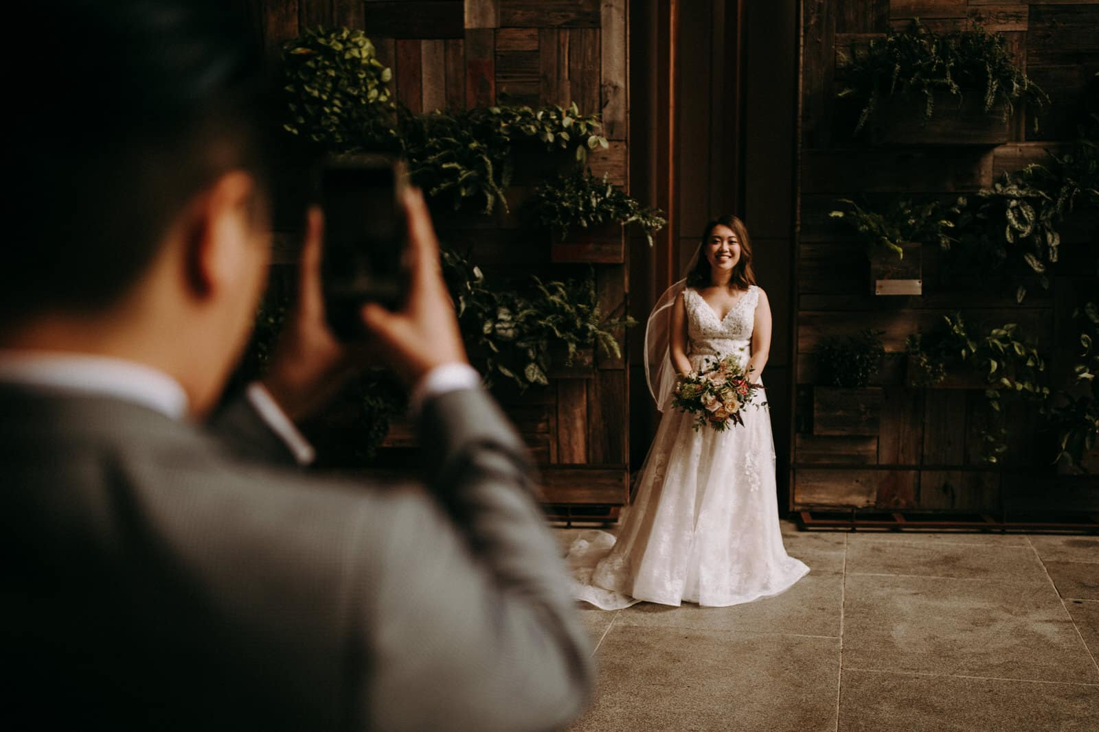 The groom is taking a picture of his bride.