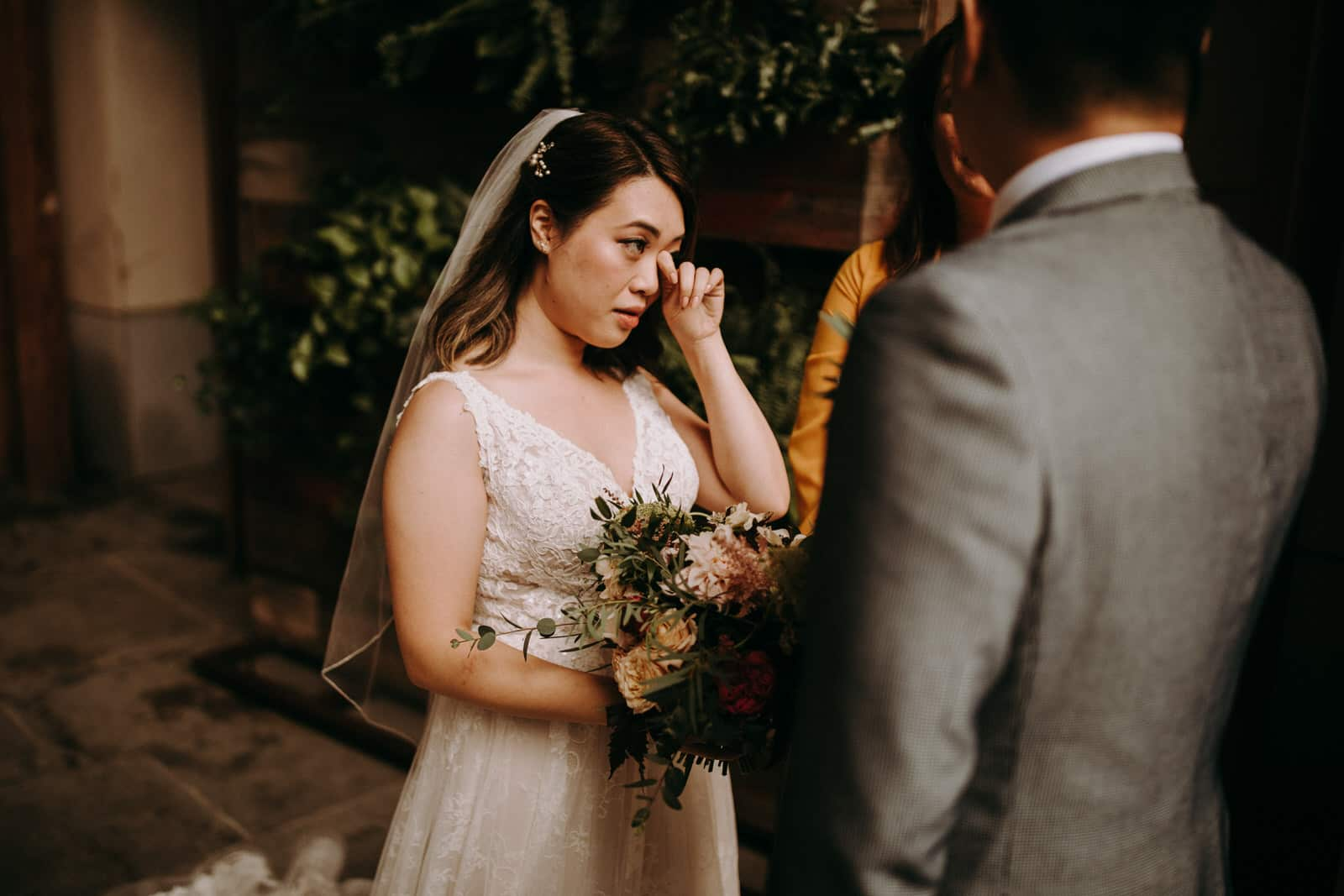 A wedding couple is getting married and the bride is getting emotional.