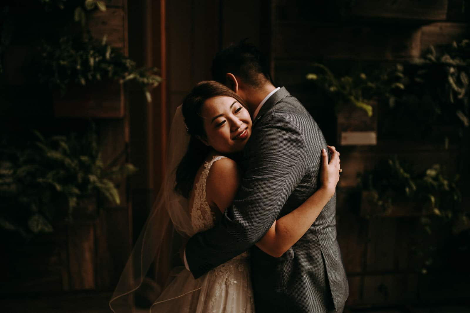A wedding couple is hugging each other.