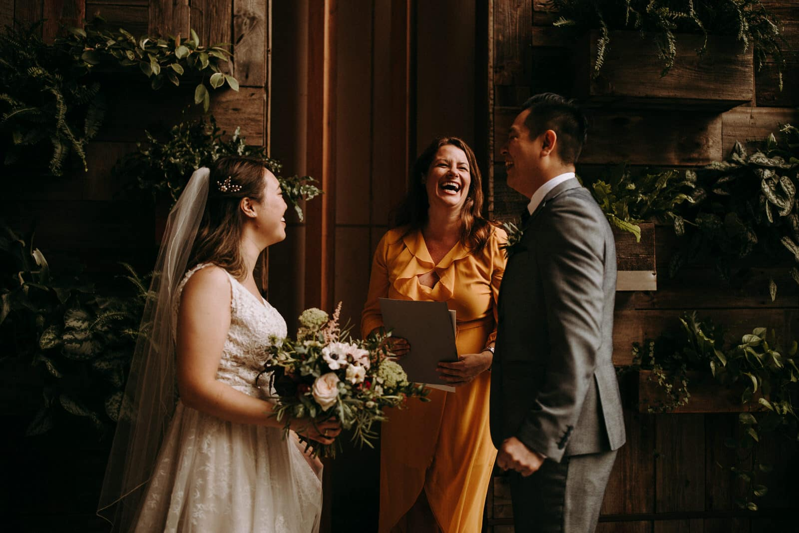 The wedding couple is about to get married and is laughing at each other with the one marrying them.
