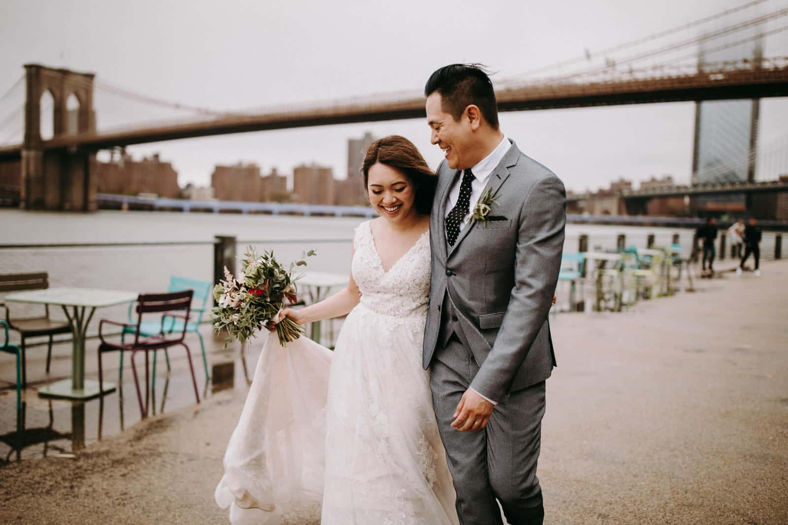 The wedding couple is walking along the esplanade right next to the Brooklyn Bridge.