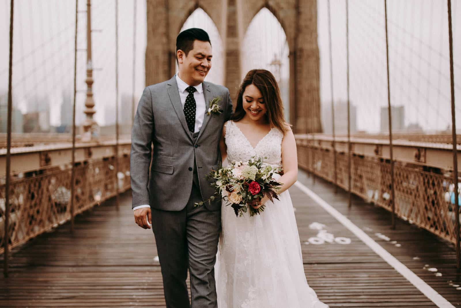 The wedding couple is walking along the Brooklyn Bridge.