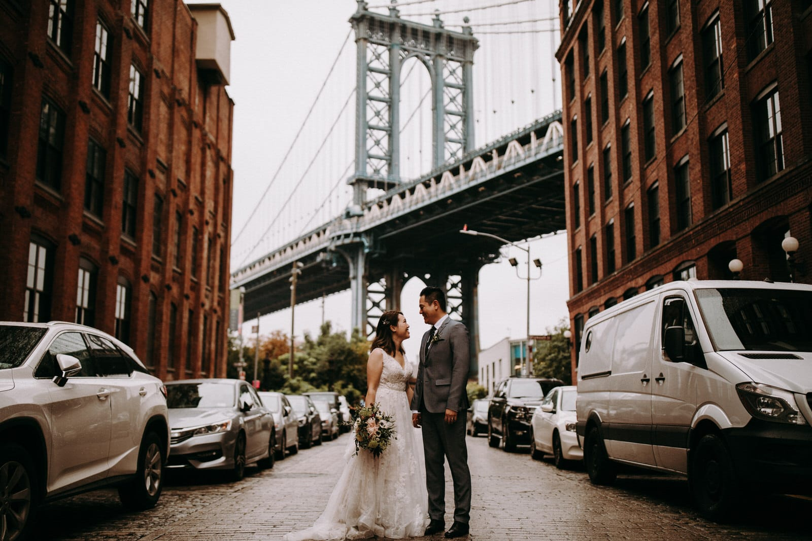 The wedding couple is standing under the Brooklyn Bridge.
