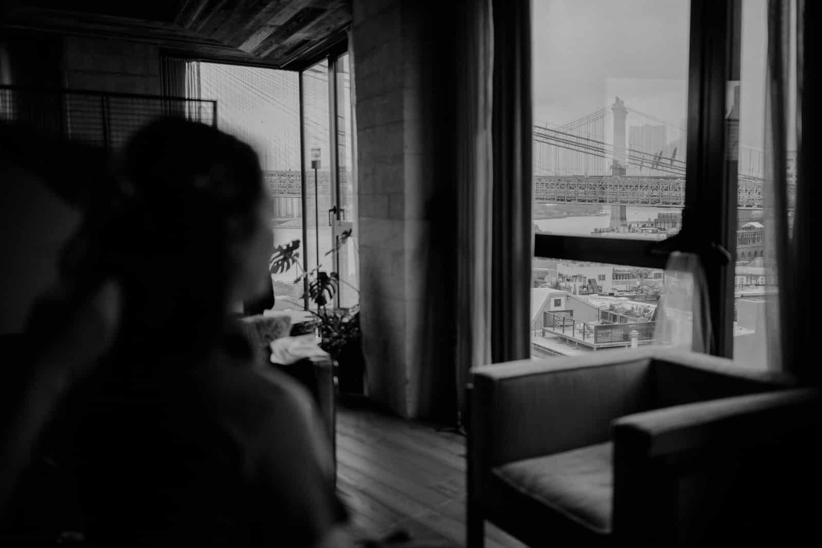 the bride is getting ready and is looking outside the window to the Brooklyn Bridge.