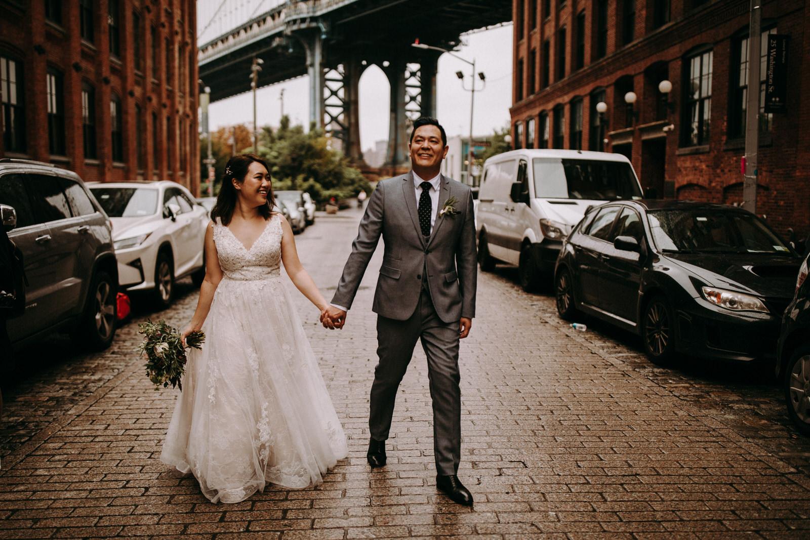 The wedding couple is walking underneath the Brooklyn Bridge.