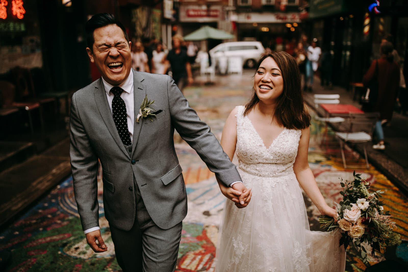 The wedding couple is laughing and walking through the streets of NYC.