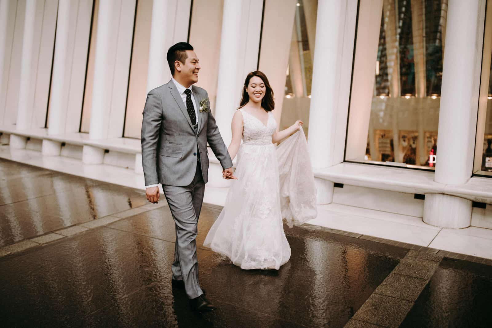 The wedding couple is walking along an architectural building.