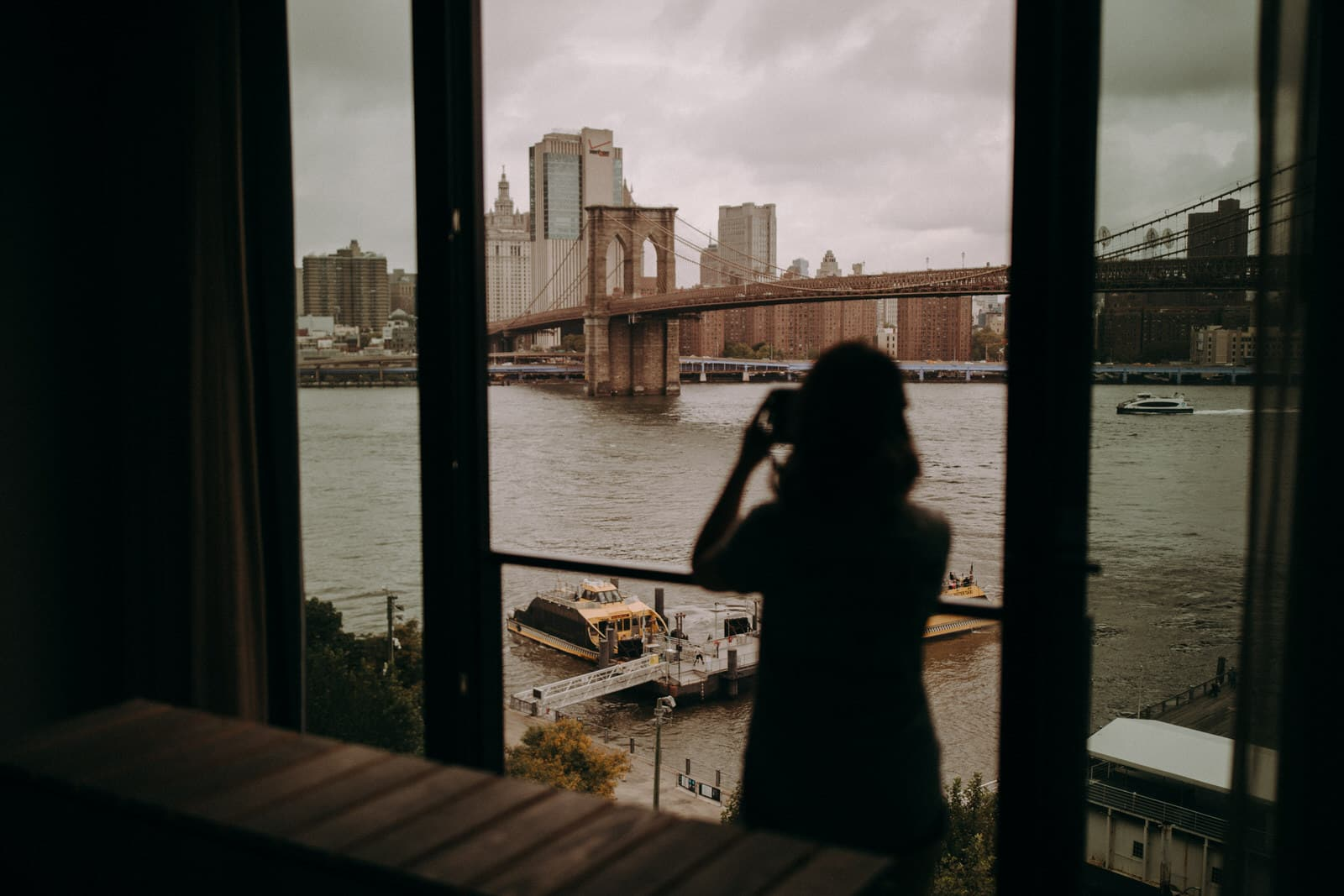 The bride is taking a picture of the Brooklyn Bridge.