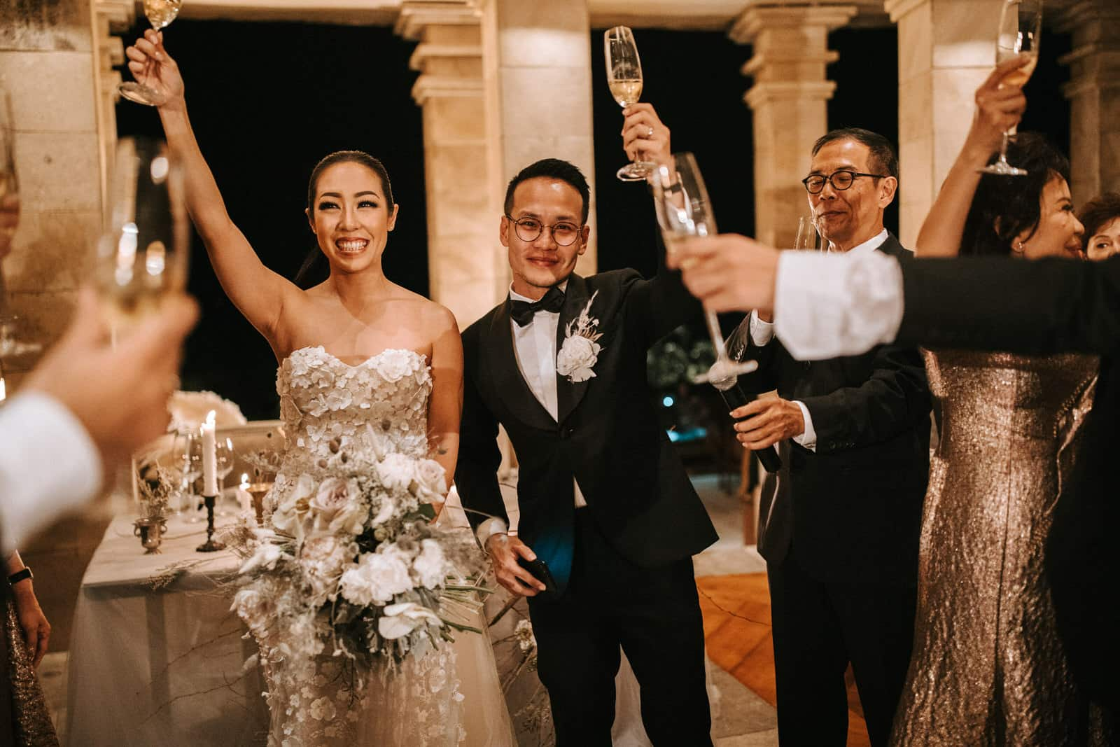 The wedding couple is holding up glasses of champagne.