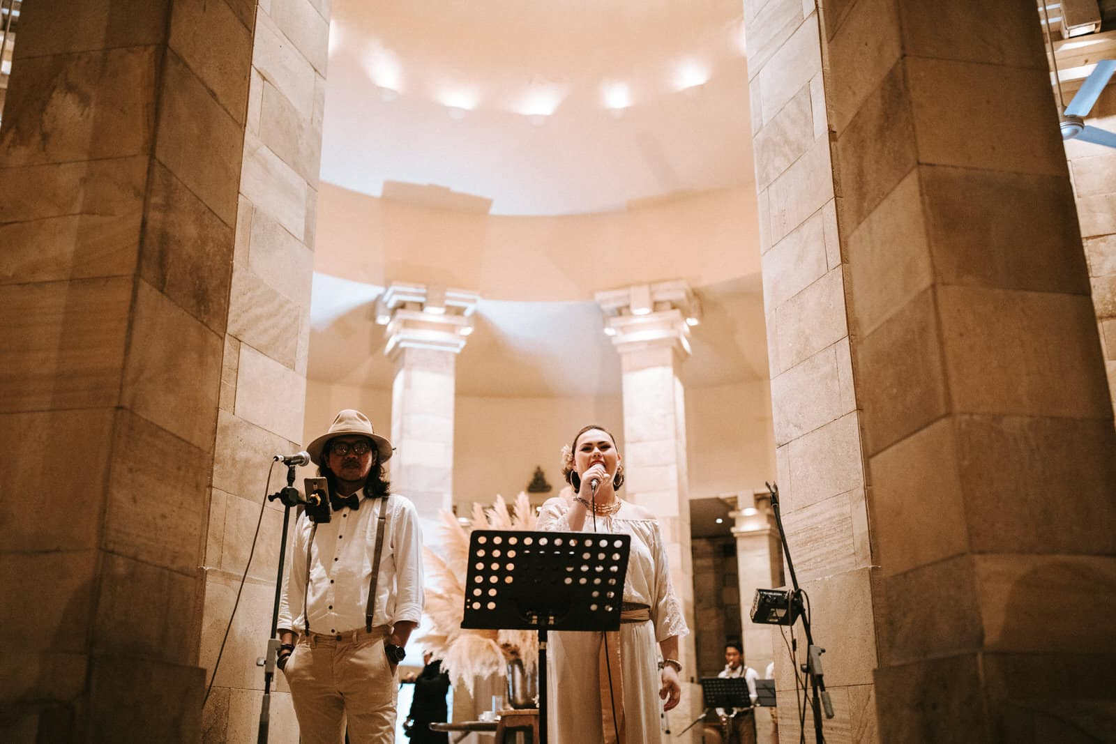 A women is singing and standing next to another singer in front of huge columns.
