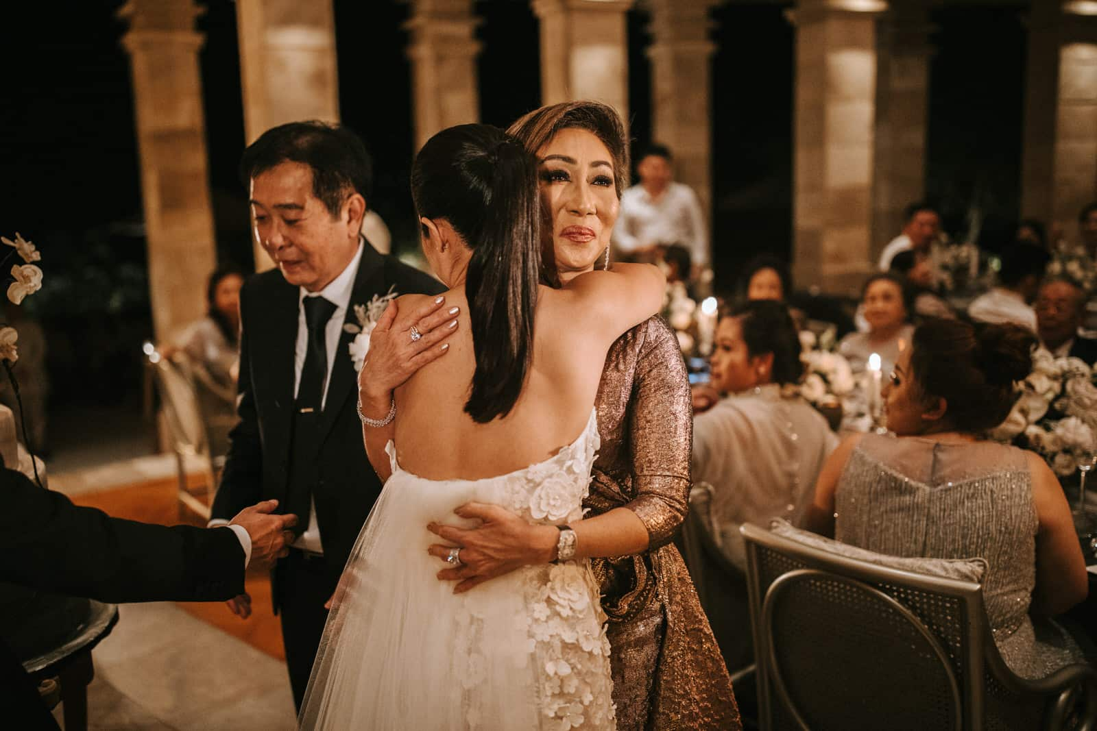The bride is hugging her mother.