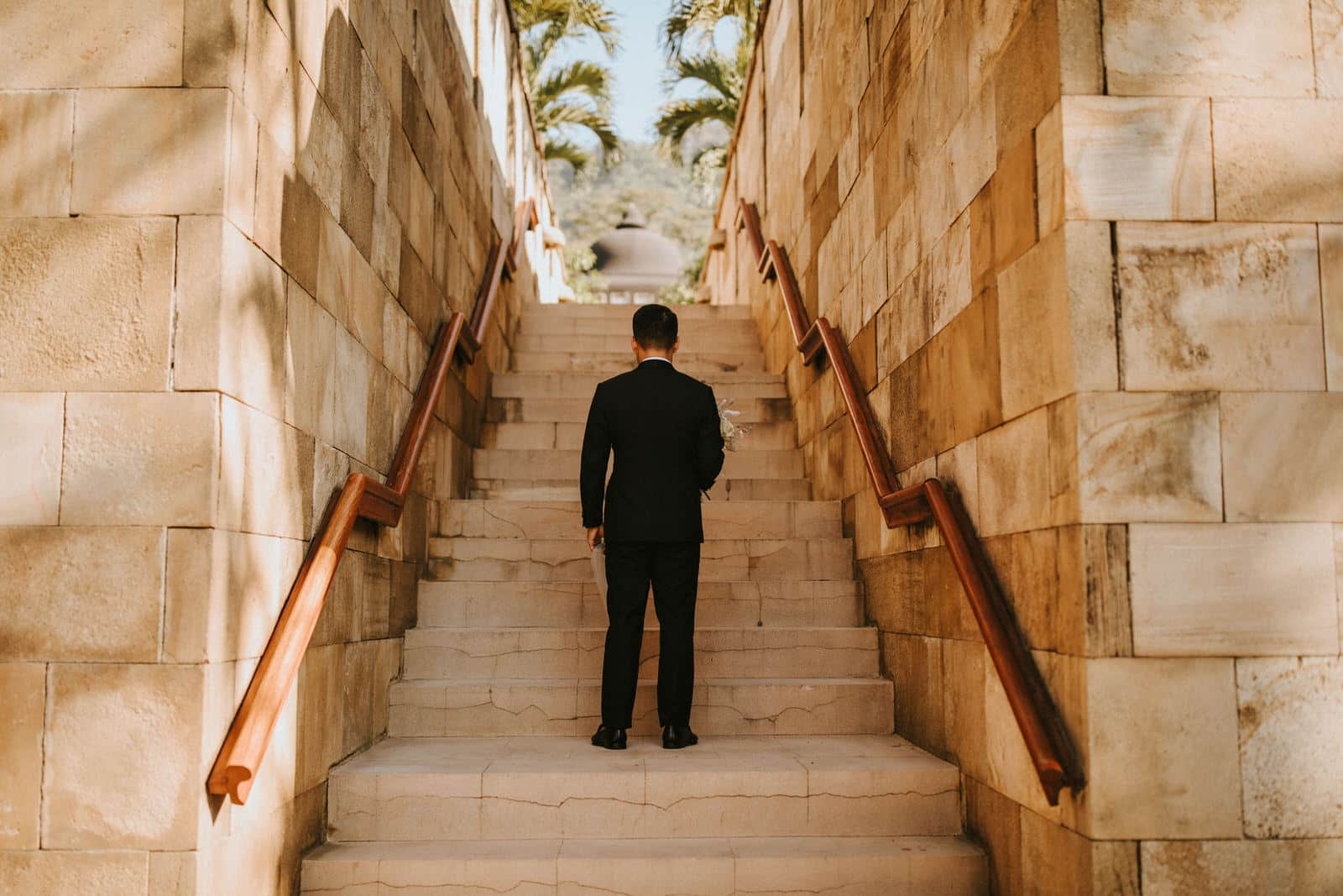 The groom is standing in the middle of stairs outside and facing away from the camera.