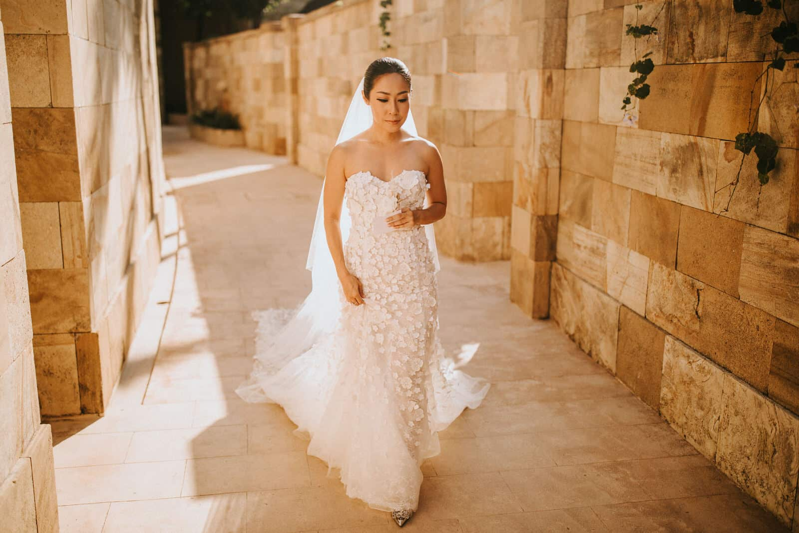 The bride is walking down an outdoor hallway.