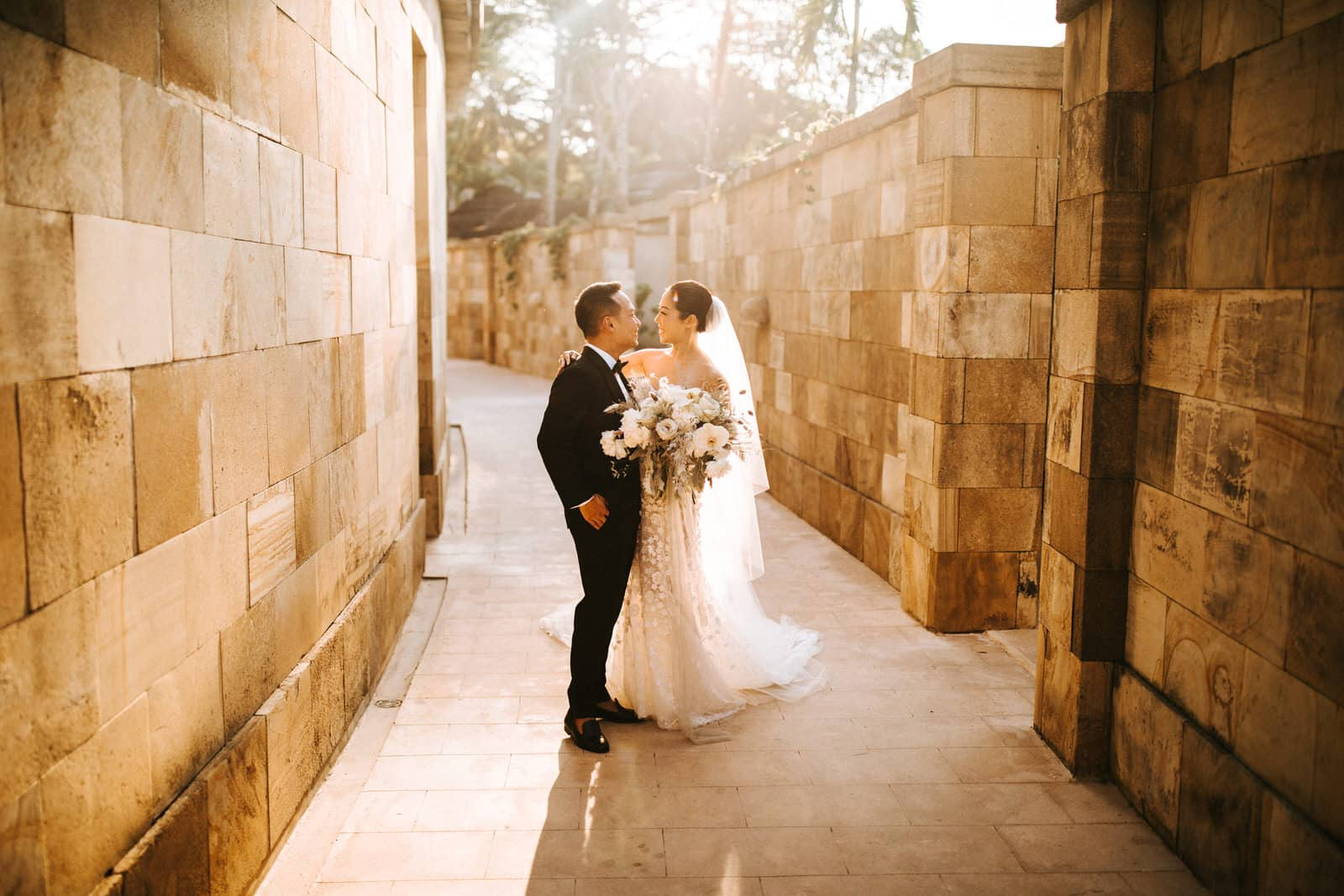 A wedding couple is standing is an outdoor hallway and is kissing.