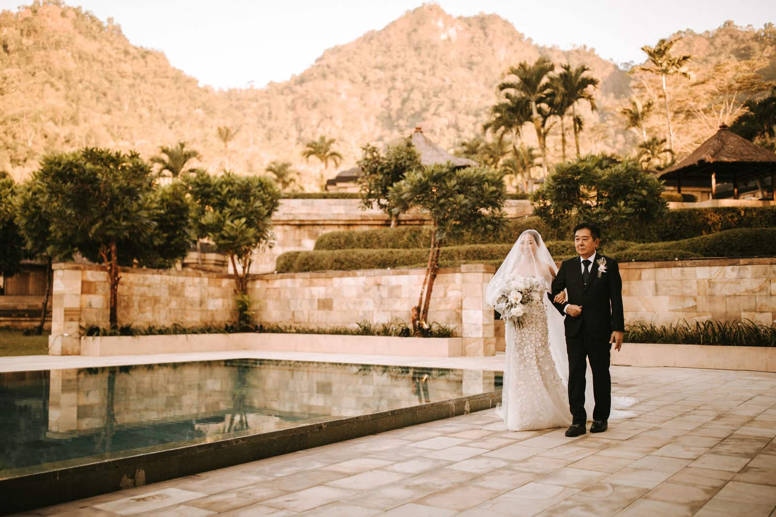 The bride and her father are walking along the pool.