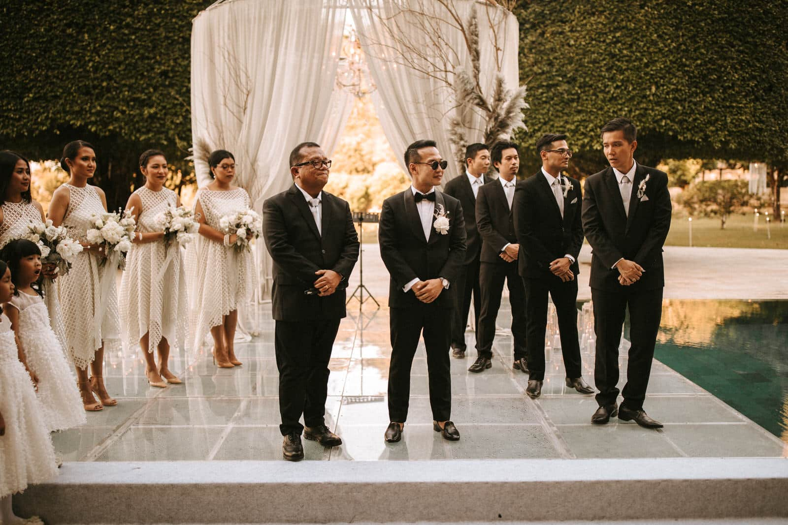 A groom and his groomsmen and the bridesmaids are waiting for the bride.