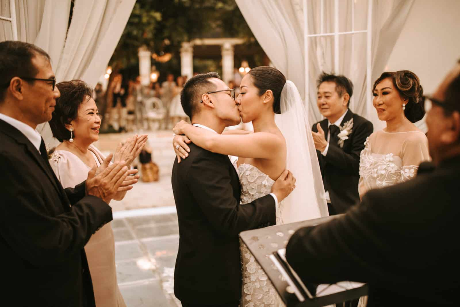The wedding couple is kissing each other.