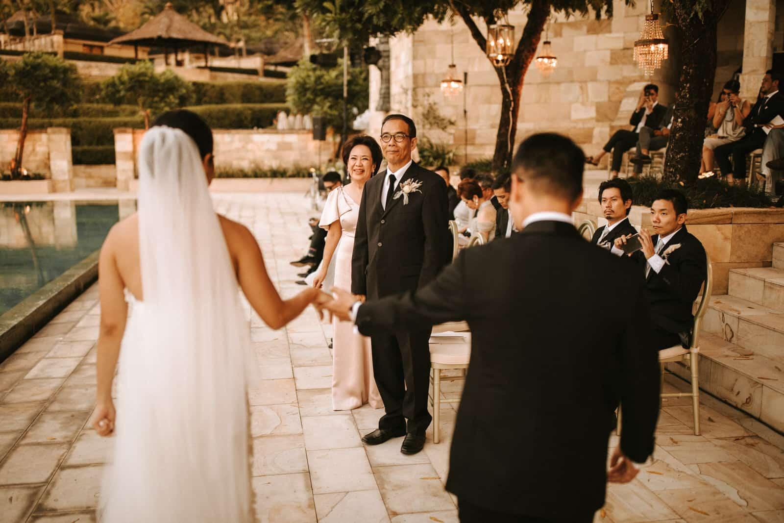 The wedding couple is holding hands and walking along their guests.