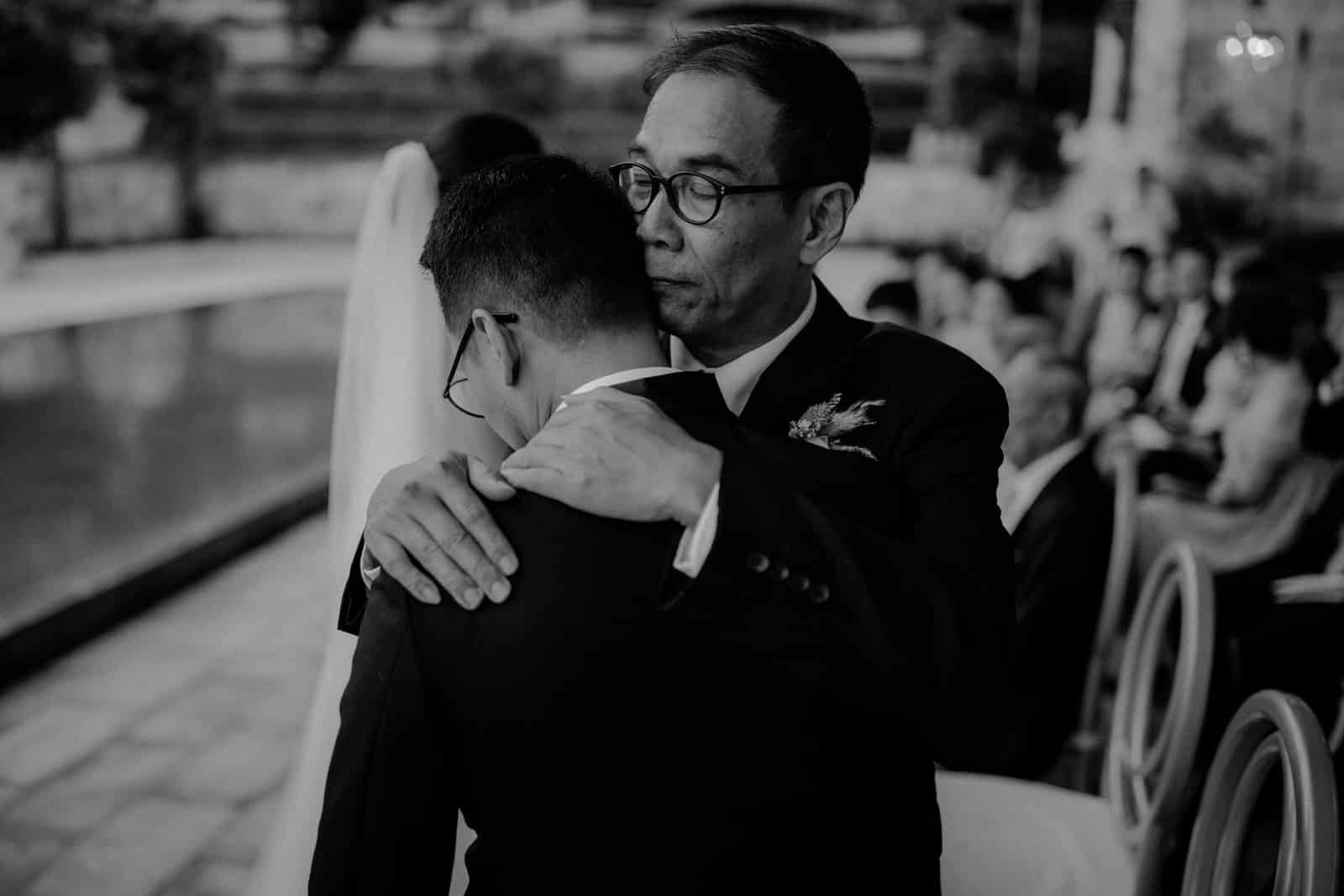 The groom is hugging a wedding guest.