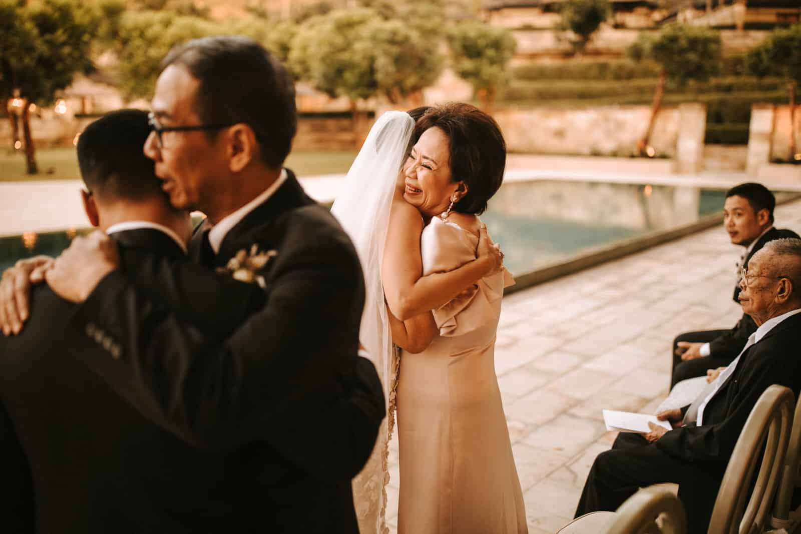 The bride is hugging a wedding guest.