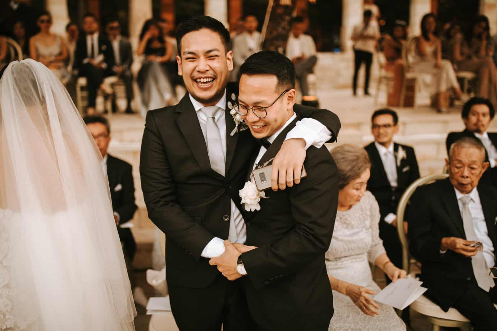 The groom is hugging his groomsman.