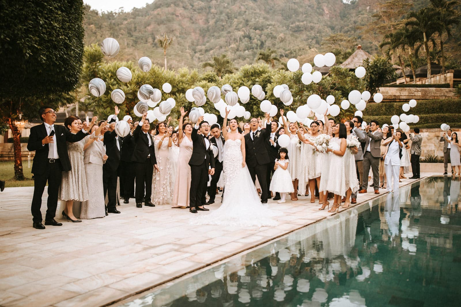 The wedding couple and their guests are releasing balloons into the air.