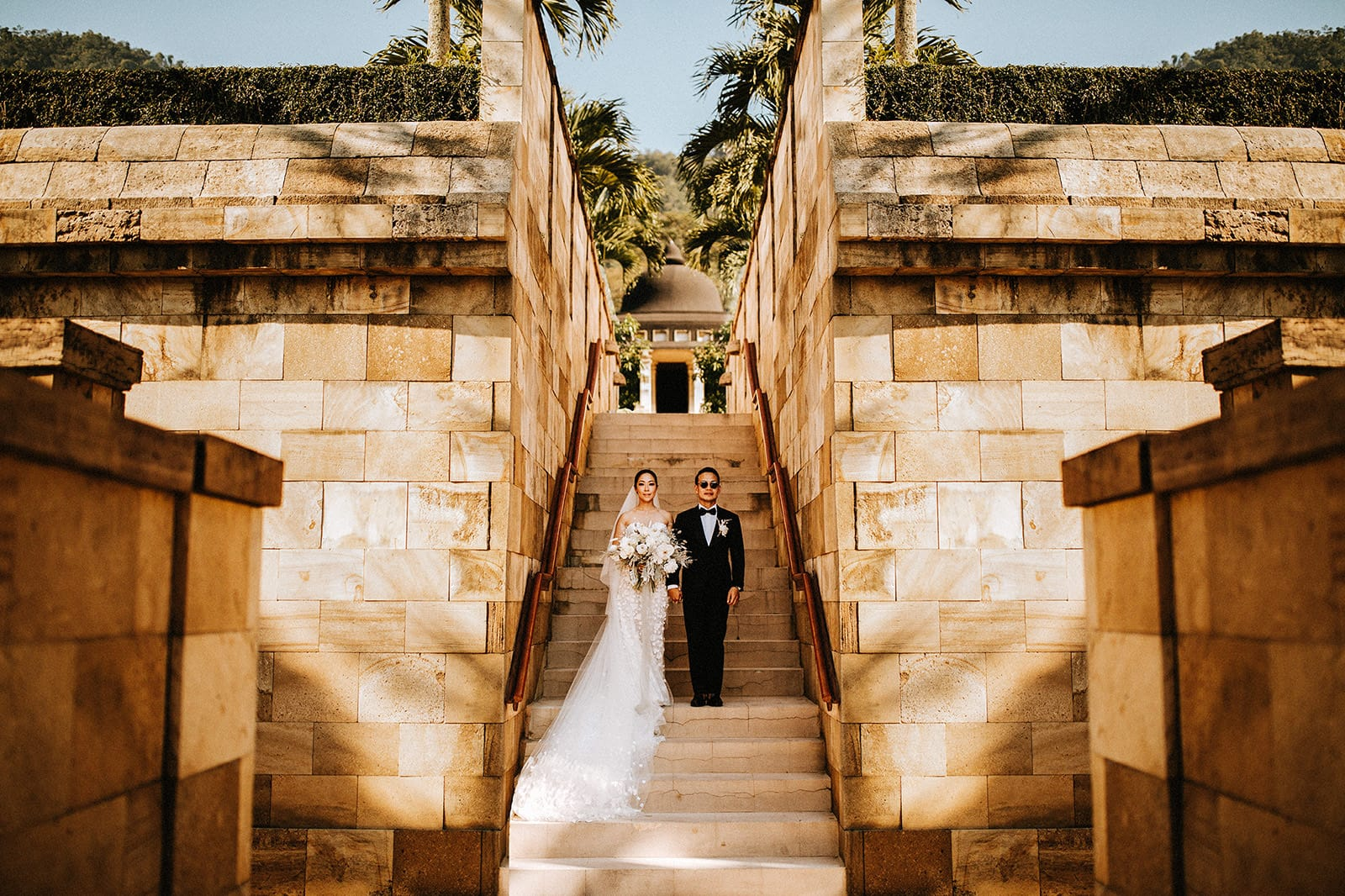 A wedding couple is standing on stairs and holding hands with an old building behind them.