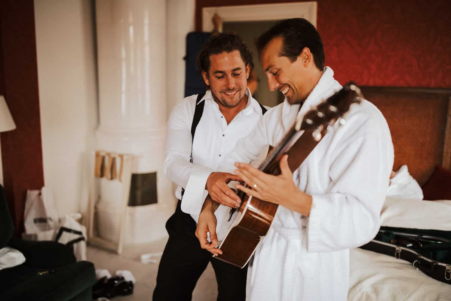 A groomsman is playing the guitar for the groom.
