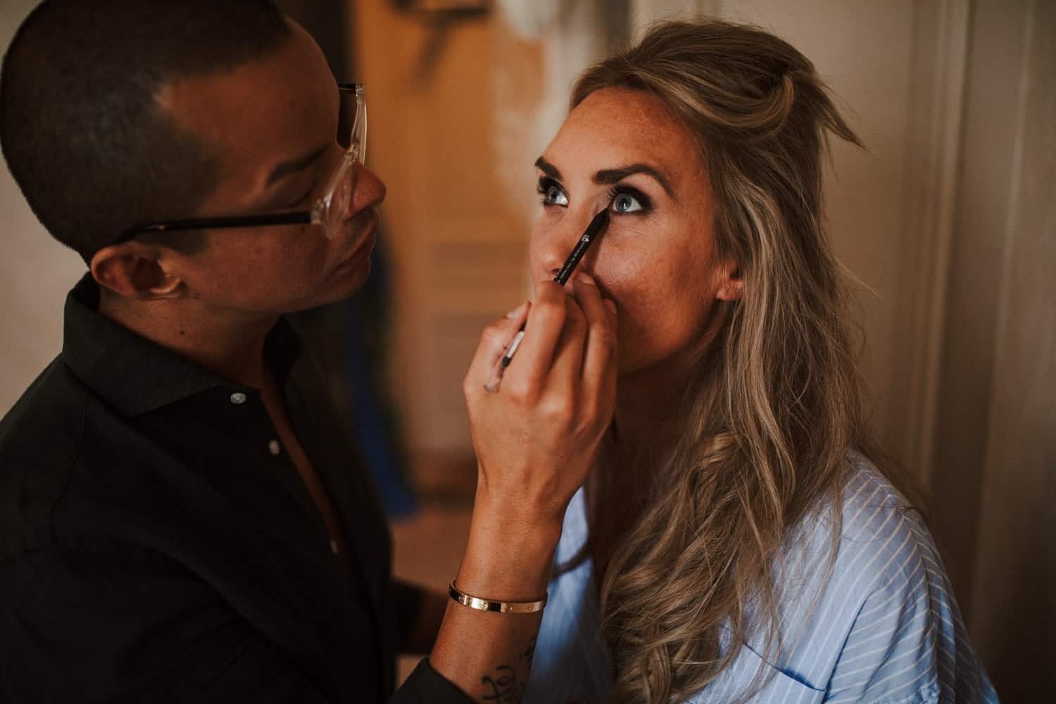 The bride is getting her makeup done.