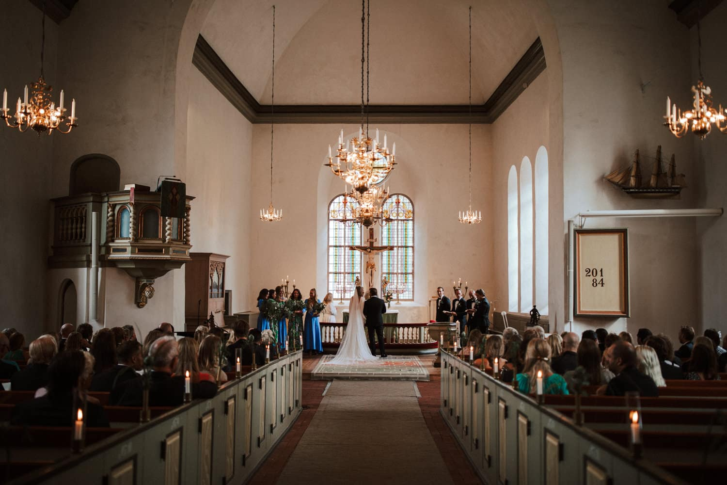 The wedding couple is standing at the end of an aisle in front of the altar in the church.