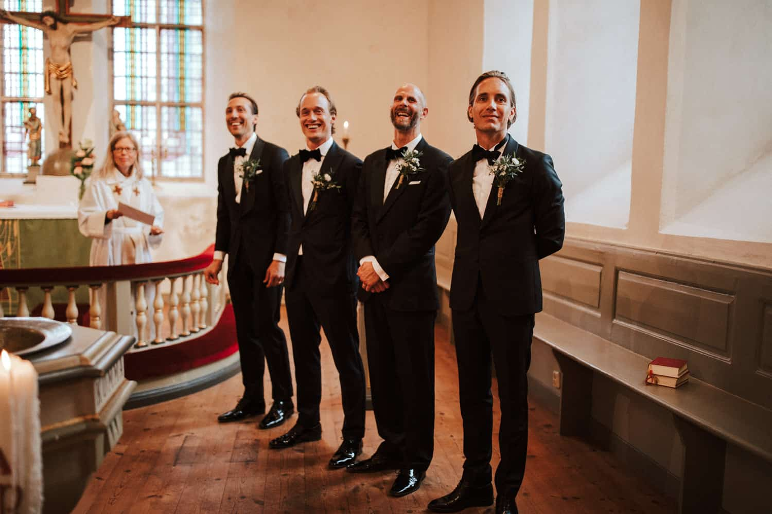 The groomsmen are standing in line and are smiling.