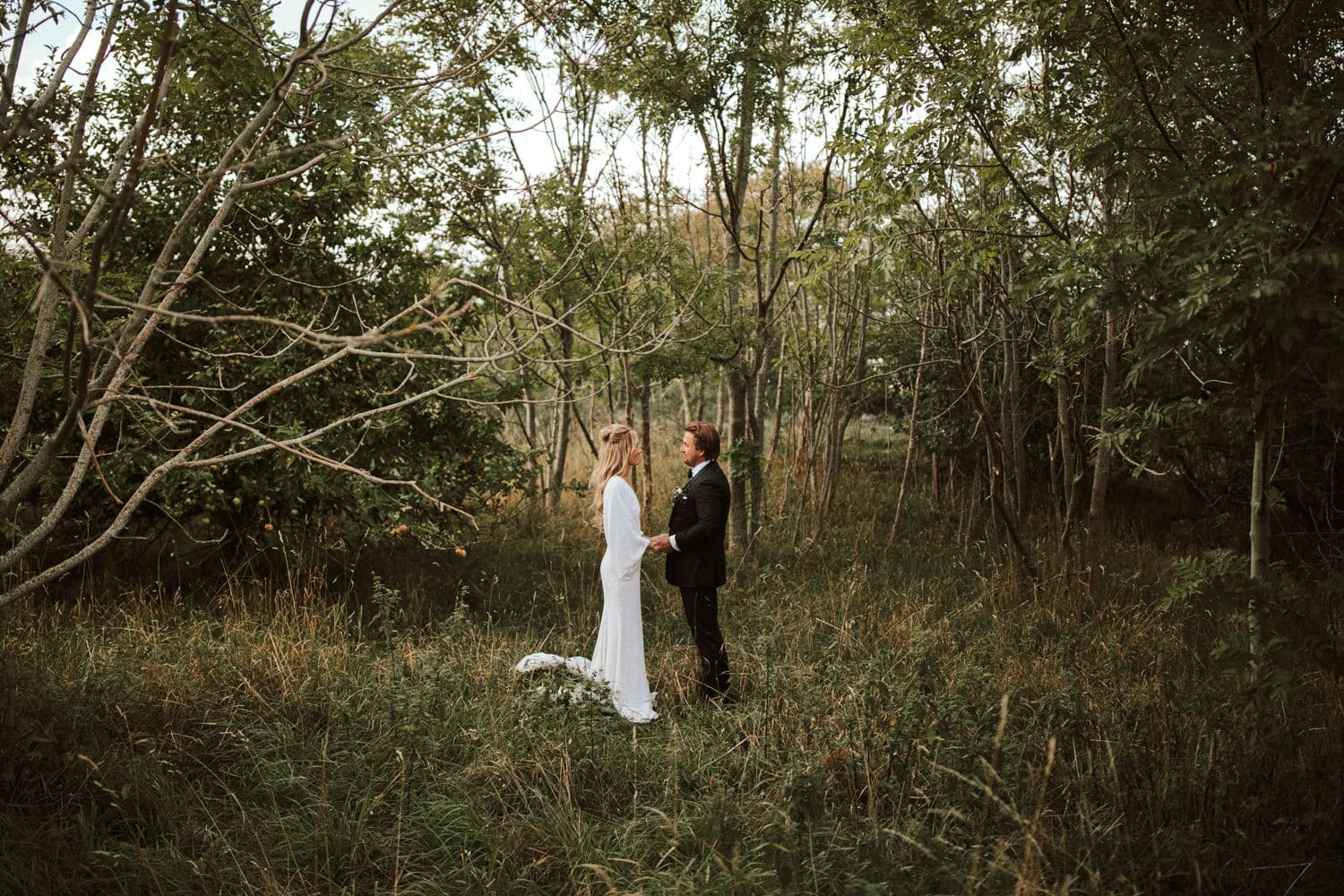 The wedding couple is walking through the meadow and is holding hands.