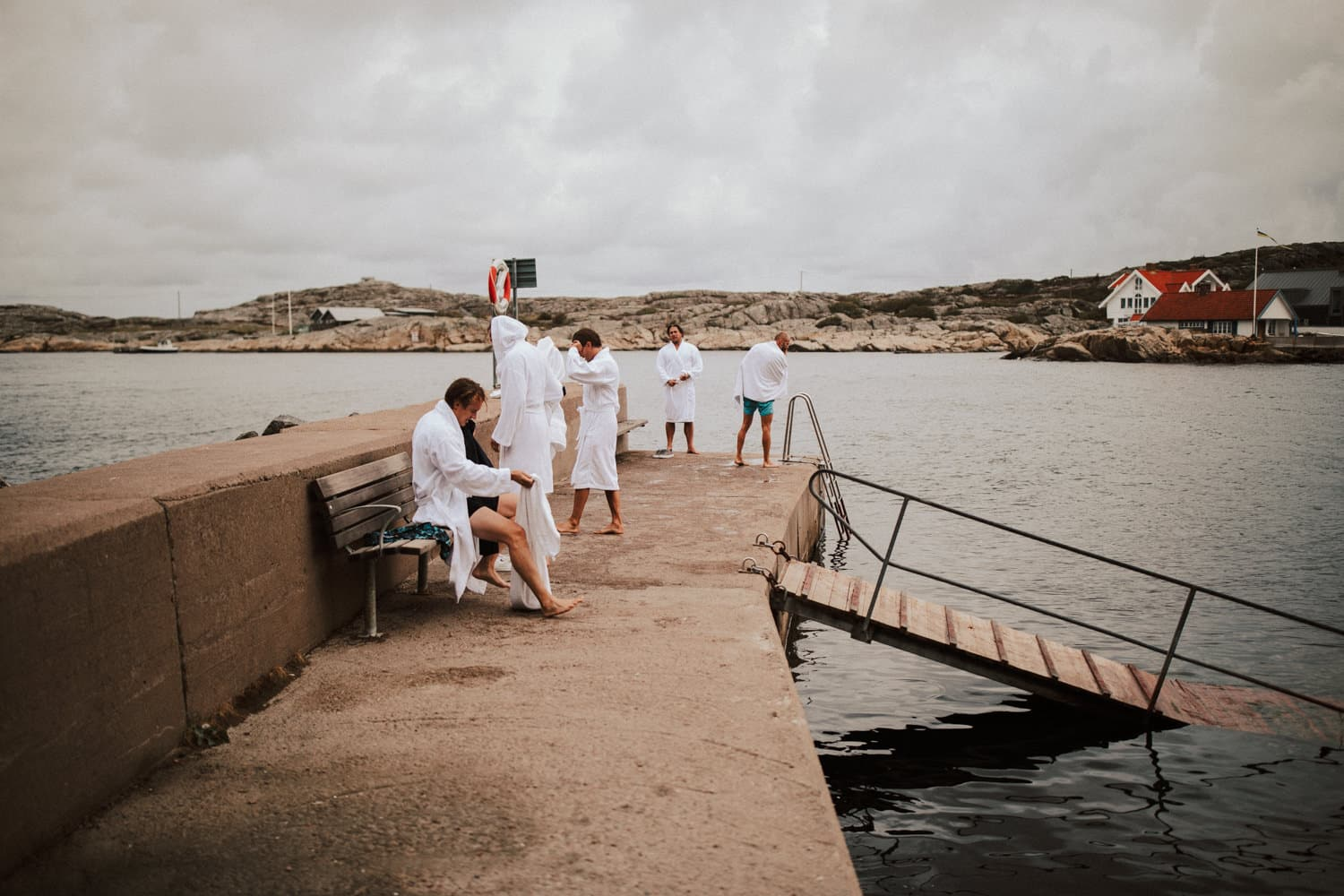 The groom and his guests are wearing white bathrobes and are standing on a platform next to the ocean.