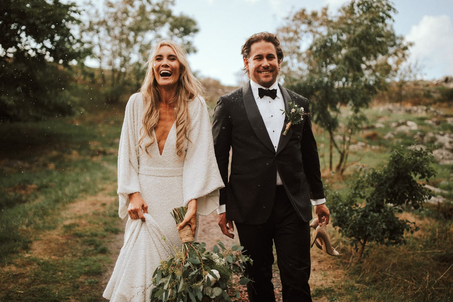 A wedding couple is walking down a path and laughing.